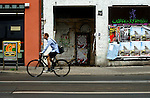 A shopping street in central Berlin, a cyclist passes a doorway which is covered with graffiti and posters.