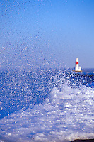 A winter wave sends spray into the air as it breaks on the Upper Harbor breakwater with the breakwater light in the background on Lake Superior in Marquette Michigan.