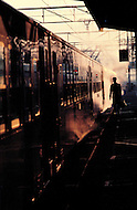 A man carrying a briefcase is about to board a train in the early morning