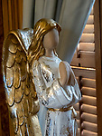 An angel statue sits on a table.