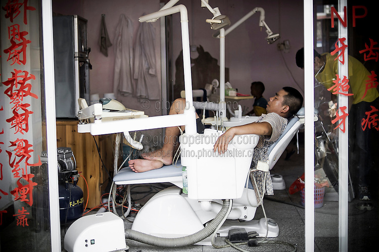 """A Chinese dentist takes a rest in his dental surgery in YangShuo near Guilin, China, August 02, 2014. <br /> <br /> This image is part of the series """"24/7"""", an ironic view on restless and fast-growing Chinese economy described through street vendors and workers sleeping during their commercial daily activity. <br /> <br /> © Giorgio Perottino"""
