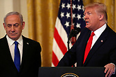 United States President Donald J. Trump speaks as Israel's Prime Minister Benjamin Netanyahu looks on during a meeting in the East Room of the White House in Washington, D.C.,on Tuesday, January 28, 2020. Credit: Joshua Lott / CNP