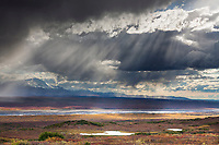 Rays of sunlight pour through stormy clouds over the tundra and McKinley river bar in Denali National Park, Alaska.