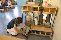 Mom helping son age 28 and 3 put on shoes after Rainbow Preschool Teczowe Przedszkole Balucki District Lodz Central Poland