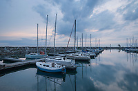 Sailing yachts moored on the mirror-still water of Meaford harbour in the early morning just before sunrise.