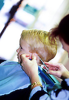 Child age 4 accepting haircut with less than modest enthusiasm.  Number 2 of a series of 3 images