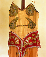 The bodice of a faded orange costume, embellished with embroidered green and gold shapes and hand-painted crescent moons
