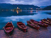 Pletna rowing boats and Lake Bled Island at twilight, Bled, Gorenjska, Slovenia, Europe