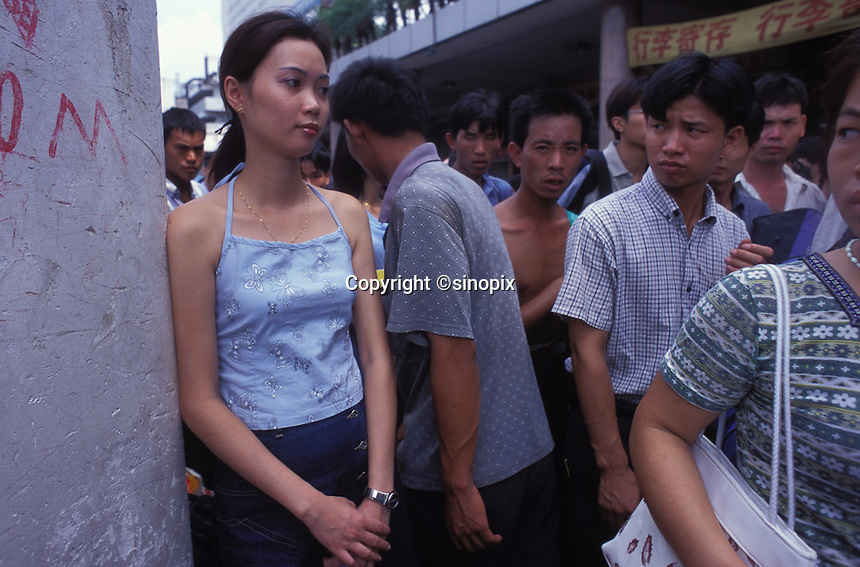 Men pass a women in Guangzhou railway Station in Guangzhou. An average gender inbalance 118 males to 100 females caused by the Chinese Governments One Child Policy and the  preference for boys means that there is a shortage of women in China.