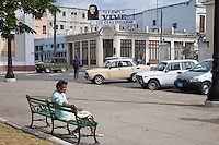 "Cuba, Cienfuegos.   Street Scene adjacent to Parque Marti.  Billboard to Che Guevara.  ""Your example lives; your ideas will endure."""