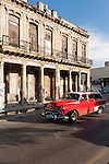 Havana, Cuba; a red classic 1954 Chevy station wagon driving down the Paseo de Marti in late afternoon sunlight