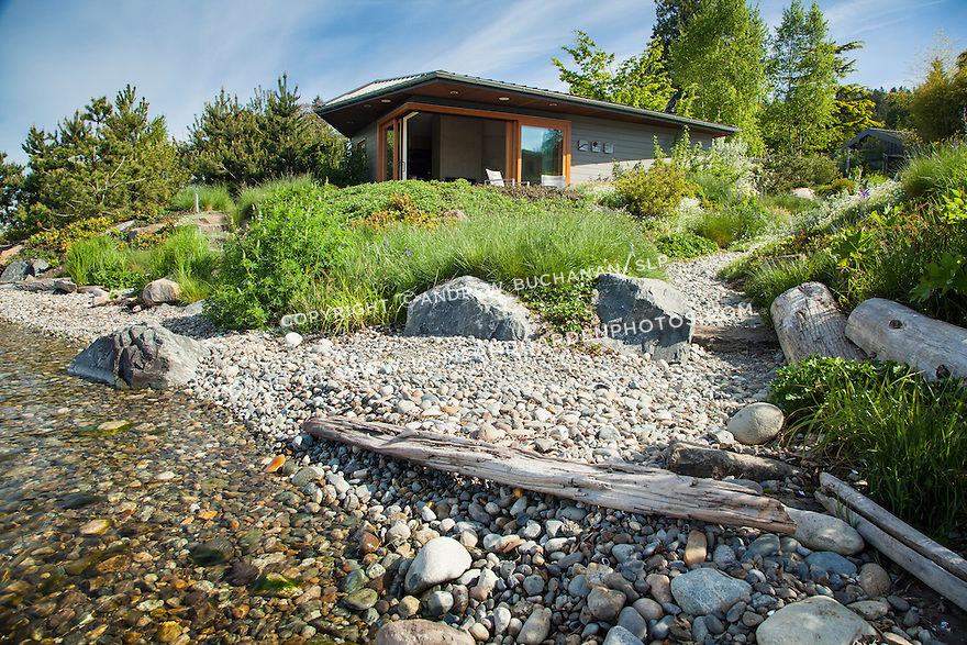 A stone path leads down from the patio to the rocky shoreline of this waterfront home.