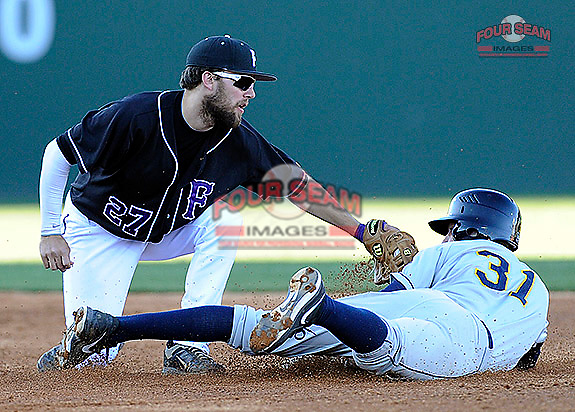 Second baseman Jordan Simpson (27) of the Furman University Paladins makes the putout as John Martillota (31) of the Toledo Rockets is caught stealing on Sunday, February 16, 2013, at Fluor Field at the West End in Greenville, South Carolina. Furman won, 13-5. The game was part of the First Pitch Invitational. (Tom Priddy/Four Seam Images)