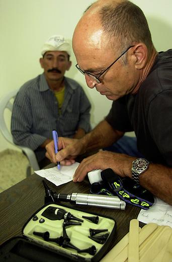 Medizinische Hilfe fuer Palaestinenser<br /> Seit Oktober 2000 ist die palaestinensische Stadt Bedia nahe Nablus nicht mehr von Israel per Auto zu erreichen. Von der israelischen Regierung aufgeschuettete Strassensperren sind fuer Fahrzeuge jeglicher Art unueberwindbar geworden. In der 10.000 Einwohnerstadt mangelt es an nahezu allem. Medizinische Versorgung gab es letztmals im Maerz diesen Jahres.<br /> Die rund 500 Mitglieder zaehlende israelisch-palaestinensische Menschenrechtsorganisation Physicians for Human Rights (PHR) hat nach einem Hilferuf des palaestinensischen Roten Kreuzes im Rathaus von Bedia eine medizinische Versorgung der Bevoelkerung durchgefuehrt (Medical Day). Rund 600 Personen konnten von 11 Aerzten und etlichen Krankenschwestern nach bis zu acht Stunden Wartezeit behandelt werden. Die Mediziner mussten an diesem Tag die dreifache Menge an Menschen versorgen. Die Patienten kamen zum Teil aus bis zu 35 km Entfernung. Das Gesundheitssytem in den palaestinensichen Autonomiegebieten ist nach Angaben der PHR seit dem Beginn der &quot;Operation Schutzschild&quot; kollabiert. Die meisten der erkrankten Kinder leiden an Atemwegs- und Viruserkrankungen.<br /> Die PHR existieren seit der ersten Intifada 1988 und haben sich zum Ziel gesetzt, in den palaestinensischen Gebieten ohne Ansehen der Herkunft und Zugehoerigkeit medizinische Hilfe zu leisten. Fuer schwer und chronisch Erkrankte versuchen die PHR-Mitarbeiter Transporte und klinische Versorgung in israelische und us-amerikanische Hospitaeler zu ermoeglichen. Bis auf zwoelf Hauptamtliche arbeiten alle anderen Mitglieder ehrenamtlich. Die Organisation finanziert sich durch Geld- und Sachspenden. Eine Zusammenarbeit mit israelischen Gesundheitsinstitutionen wird von Regierungsseite abgelehnt.<br /> Bedia / Israel, 18.05.2002<br /> Copyright: Christian-Ditsch.de<br /> [Inhaltsveraendernde Manipulation des Fotos nur nach ausdruecklicher Genehmigung des Fotografen. Vereinbarungen ueber Abtretung von Persoe