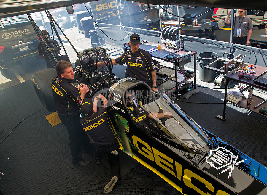 Jun. 1, 2014; Englishtown, NJ, USA; NHRA top fuel driver Richie Crampton warms up his car surrounded by crew members during the Summernationals at Raceway Park. Mandatory Credit: Mark J. Rebilas-