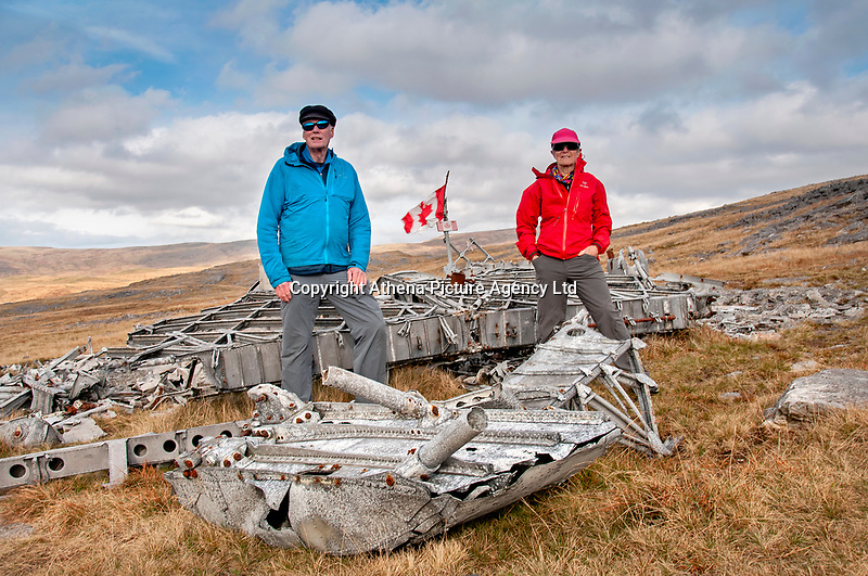 """Pictured: Dr Peter Pare (L) with his wife by the wreckage of the Wellington Bomber MF509 in the Brecon Beacons, Wales, UK. <br /> Re: The nephew of a World War II airman whose plane crashed into a Welsh mountain has climbed the peak to pay tribute to the uncle he never met.<br /> Dr Peter Paré, 74, travelled from his home in Vancouver, Canada, to read a poem at the desolate spot where his uncle Bill Allison was killed.<br /> Flying officer Allison, 28, was one of the six crew of a Wellington Bomber that crashed on a training flight in November 1944.<br /> The plane wreckage is still scattered over Carreg Goch in the Brecon Beacons where hundreds of young airmen learned to prepare for bombing missions.<br /> Dr Paré said: """"I wanted to make this pilgrimage even though I was a baby when he died and never met Bill Allison.<br /> """"We only found out about the crash site recently and it is remarkable that so much of the plane is still here.""""<br /> Flying officer Allison was the oldest on board when the plane's starboard engine developed a fault during a low-flying exercise.<br /> For years local people have honoured the brave airmen by flying a Canadian flag at the scene - replacing it every time it gets ripped by strong winds.<br /> Dr Paré, retired Professor of Medicine at the University of British Columbia, said: """"It was very moving to see the Maple Leaf flying where my uncle died all those years ago.<br /> """"It brought a tear to my eye as I read the poem I wrote in his honour."""""""