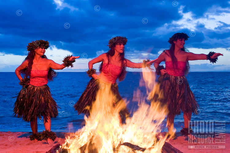 Three hula dancers perform a dance for Pele next to a fire on the beach at Makena, Maui.