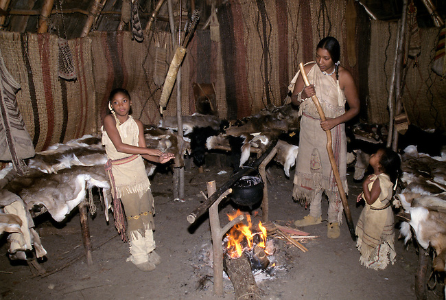 Native American family of mother and two daughters dressed in historic clothing inside a traditionally furnished Wampanoag longhouse with cooking fire