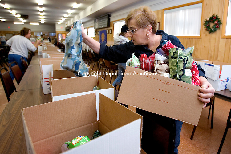 WOLCOTT, CT 08 December 2008-120808SV03--Sylvia Ouellette of Wolcott helps to fill 90 boxes of Christmas presents for troops serving in Iraq at the American Legion in Wolcott. Operation Hometown Support, a group of several Wolcott volunteers, were packaging the Christmas presents Monday.<br /> Steven Valenti Republican-American