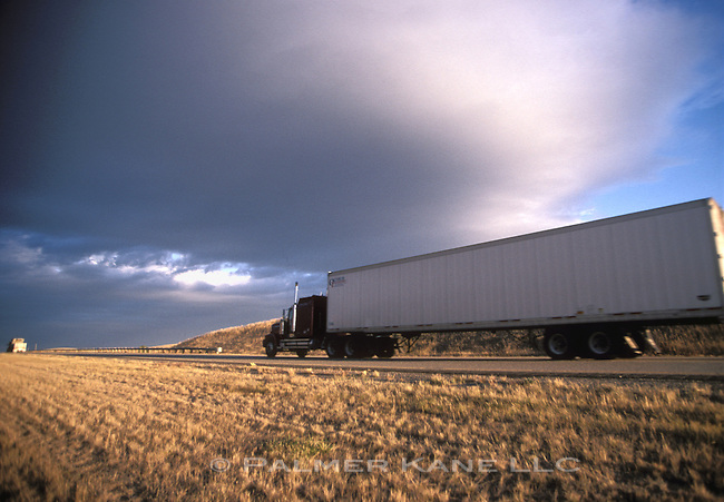 18 Wheeler truck driving through wheat field on rural road
