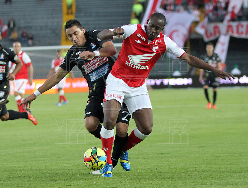 BOGOTA -COLOMBIA- 6 -10--2013.Juan Caicedo (Der) de Independiente Santa Fe disputa el balon contra Jonathan Lopera (Izq)  de Once Caldas, partido correspondiente a la catorceava  fecha de La Liga Postobon segundo semestre jugado en el estadio El Campin / Juan Caicedo (R) of Independiente Santa Fe dispute the ball against Jonathan Lopera (L) of Once Caldas, the fourteenth game in La Liga Postobon date second half played at El Campin.Photo: VizzorImage / Felipe Caicedo / Staff