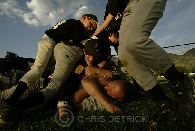 "Centerville, UT--24 Jun 2005--.**Close Up**.The members of the winning Centerville Rockies celebrate by ""dog piling"" their coach Stacey Remington after defeating the Rangers.  The Rockies started the tradition of piling onto the coach three years ago and continue to do this after every victory. .The Rockies defeated the Rangers 7-4 in the 11-12 year old .Davis County Little League world series qualifying game Friday evening.  .Chris Detrick /Salt Lake Tribune.File #Little League CD01"