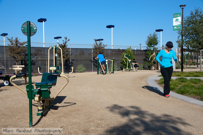 Multiple people out in the morning using the bodyweight based exercise equipment at Stanton Central Park.