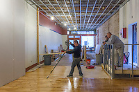 Worker applies a sealer to recently restored wood flooring at a restaurant construction site in Uptown Westerville.