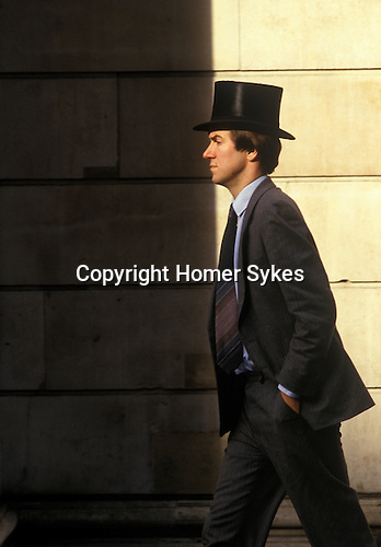 Runner at the London Stock Exchange wearing the traditional top hat. City of London. England. Circa 1980