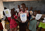 Children hold signs for different letters of the alphabet during a class in the Catholic Church-sponsored St. Daniel Comboni Primary School in Lugi, a village in the Nuba Mountains of Sudan. The area is controlled by the Sudan People's Liberation Movement-North, and frequently attacked by the military of Sudan. The church has sponsored schools and health care facilities throughout the war-torn region.