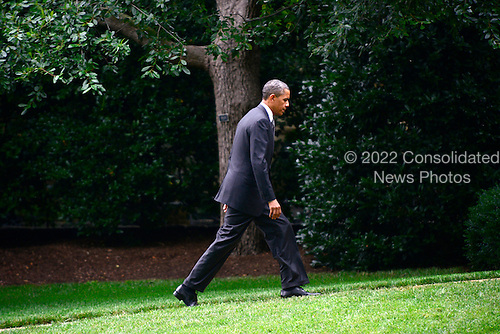 United States President Barack Obama walks towards the Oval Office after arriving on the South Lawn of the White House in Washington, D.C. on Friday, July 20, 2012.  The President was scheduled to spend most of the day campaigning in Florida but cut the trip short following the mass murder in Aurora, Colorado last night..Credit: Ron Sachs / Pool via CNP