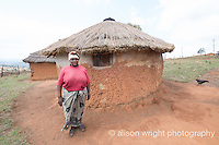 Africa, Swaziland, Malkerns. Woman in front of her thatched roof home.