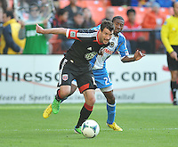 Chris Pontius (13) of D.C. United goes against Raymon Gaddis (28) of the Philadelphia Union. The Philadelphia Union defeated D.C. United 3-2, at RFK Stadium, Sunday April 21, 2013.