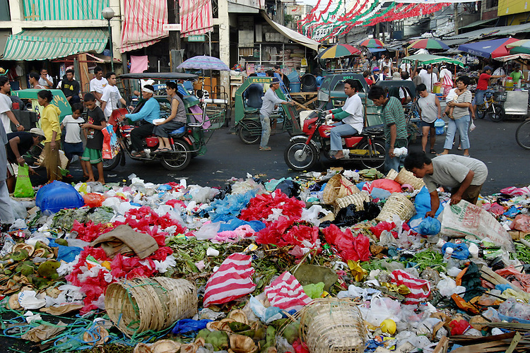 """Outside the Quiapo Market in the Philippines, people pick through the trash discarded from the early-morning wholesale market. Inside, the covered market is a tumult of activity and offers an extraordinary variety of goods, ranging from food, clothing, consumer electronics, and patent medicines to religious images and even prayers (busy people can outsource their prayers to the Quiapo Church's """"prayer ladies""""). Hungry Planet: What the World Eats (p. 239). This image is featured alongside the Cabaña family images in Hungry Planet: What the World Eats."""