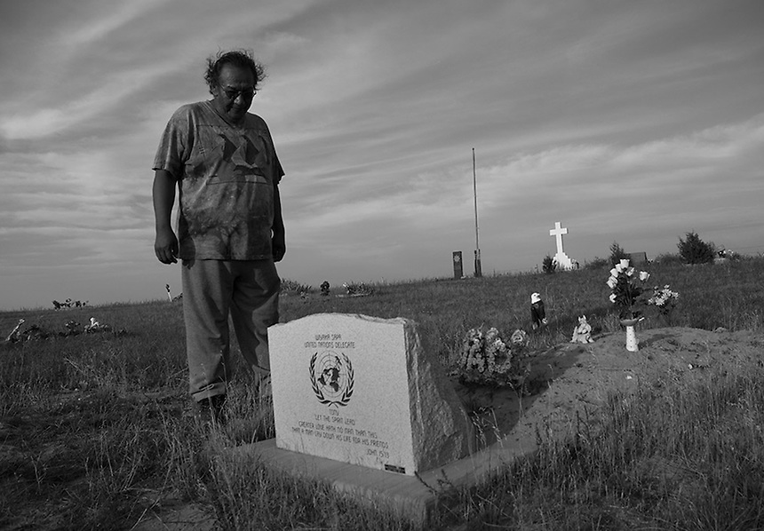 Garvard Good Plume on the grave of his uncle Anthony Black Feather at the Woolf Creek cemetery. The Lakota man was a spokesperson for the Teton Sioux Nation Treaty Council and worked at  the United Nations advocating for Indigenous rights.