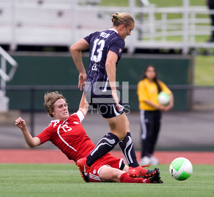 Christie Welch (13) of the Washington Freedom has the ball tackled away from her by Sophie Schmidt (13) of Canada during a friendly at George Mason University in Fairfax, Va.  Canada tied the Washington Freedom, 3-3.