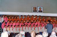 School choir giving recital overlooked by portraits of party officials. Pictures taken in Canton China in 1977 at the time of the cultural revolution.