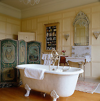 A hand-painted folding screen shields the free-standing bath from the door in this wood panelled bathroom