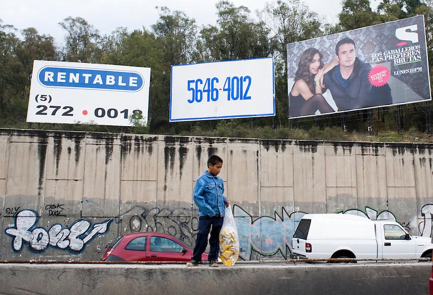 A child sells crisps in traffic in Santa Fe, Mexico City.
