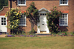 Roses grow around the door of a country cottage, Shottisham, Suffolk, England