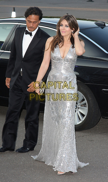 ARUN NAYER & ELIZABETH HURLEY.The Caudwell Children Butterfly Ball at Battersea Evolution, London, England. .May 20th, 2010 .full length liz married husband wife black tuxedo silver dress low cut neckline cleavage clutch bag maxi hand.CAP/ROS.©Steve Ross/Capital Pictures.