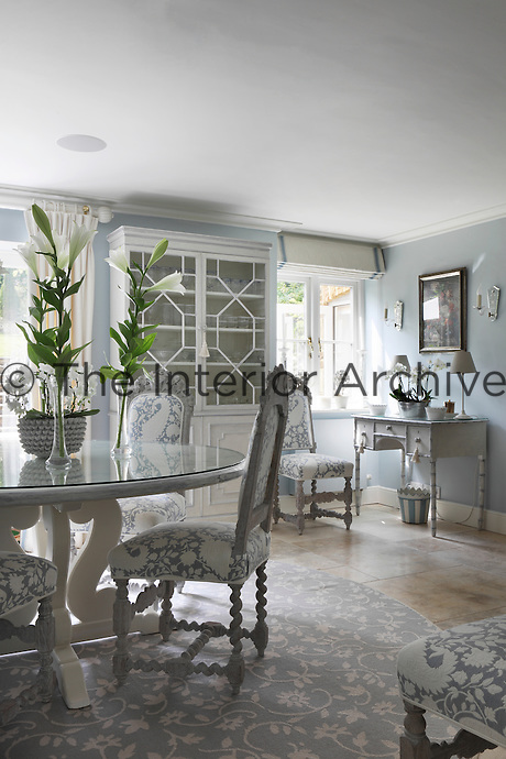 A dining room with pale grey and white patterned furniture and circular rug