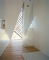 The open plan shower room is punctuated by a triangular-shaped window
