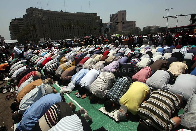 Egyptian protesters perform the weekly Friday noon prayer in Cairo's landmark Tahrir square during a demonstration against Egyptian presidential runoff candidate Ahmed Shafiq, an ex-prime minister under the ousted regime of Hosni Mubarak, on June 1, 2012. Earlier this week, attackers set fire to Shafiq's headquarters following the announcement that he was to face the Muslim Brotherhood candidate Mohammed Mursi in the second round of Egypt's presidential election on June 16-17. Photo by Ashraf Amra