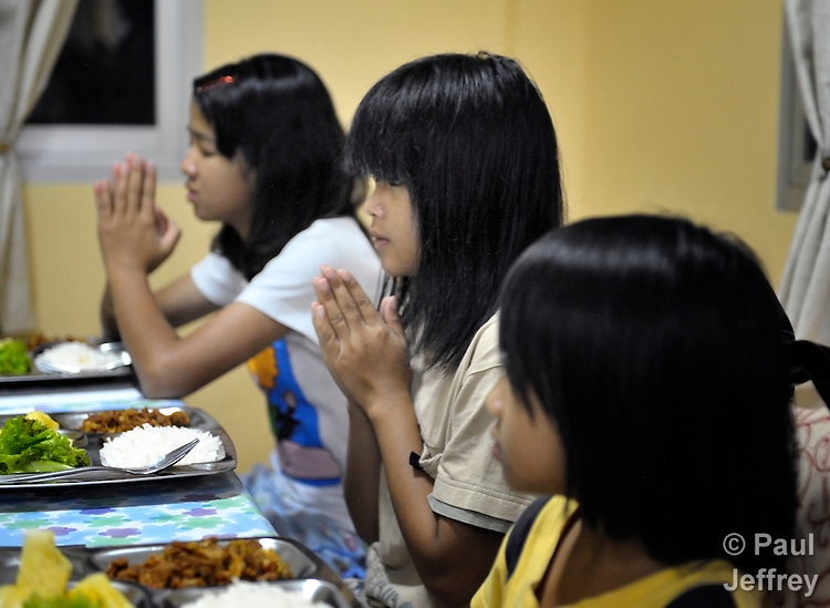 Girls pray at mealtime in an orphanage in Chiang Mai, Thailand. The girls are HIV positive. The orphanage was started by United Methodist missionaries.
