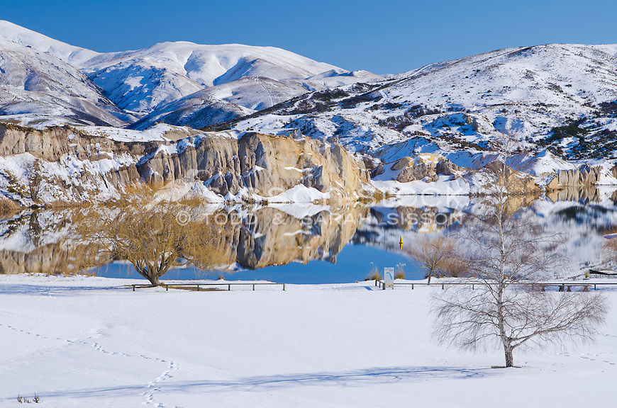 Blue Lake reflection with snow on a blue sky, winters day, St Bathans, Central Otago, New Zealand