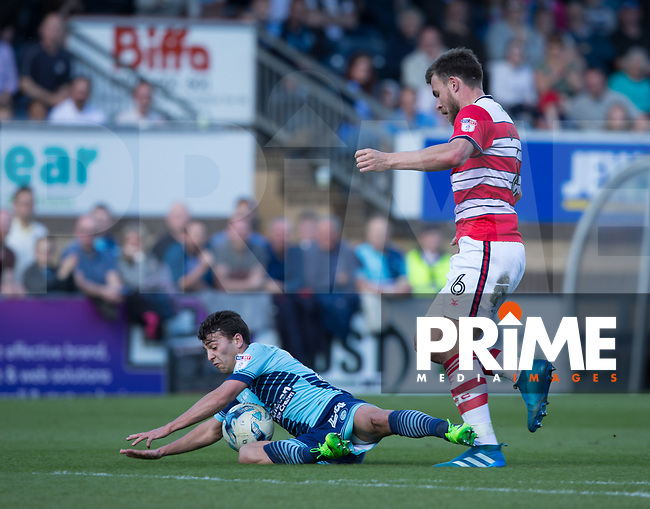 Scott Kashket of Wycombe Wanderers is brought down by Andy Butler of Doncaster Rovers during the Sky Bet League 2 match between Wycombe Wanderers and Doncaster Rovers at Adams Park, High Wycombe, England on 22 April 2017. Photo by James Williamson / PRiME Media Images.