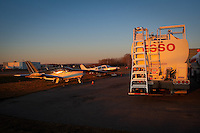 The sun set on a Esso oil truck and two small aircraft at the Quebec City Jean Lesage International Airport, also known as Jean Lesage International Airport (French: Aeroport international Jean-Lesage de Quebec, or Aeroport de Quebec) (IATA: YQB, ICAO: CYQB) November 11, 2009.