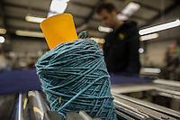 Bobina di filo azzurro in primo piano e operaio al lavoro sfocato sullo sfondo Bute tartan mills