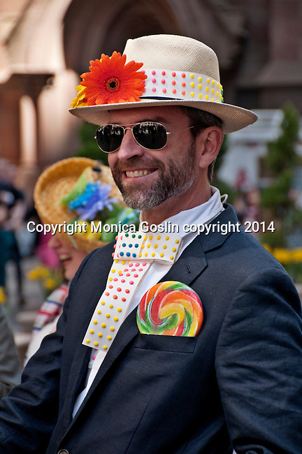 Man in a suit with a tie made out of candy, candy on his straw hat, and a lollypop in his pocket smiles in the Easter Parade on Fifth Avenue in New York City